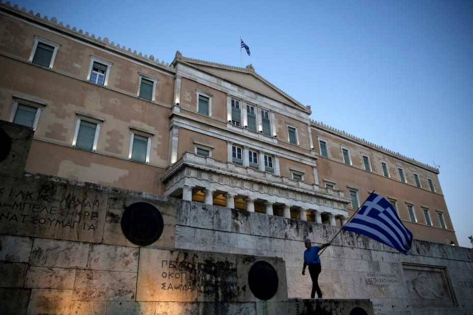 FILE PHOTO: A man waves a Greek flag during an anti-goverment rally outside the Greek parliament building in Athens