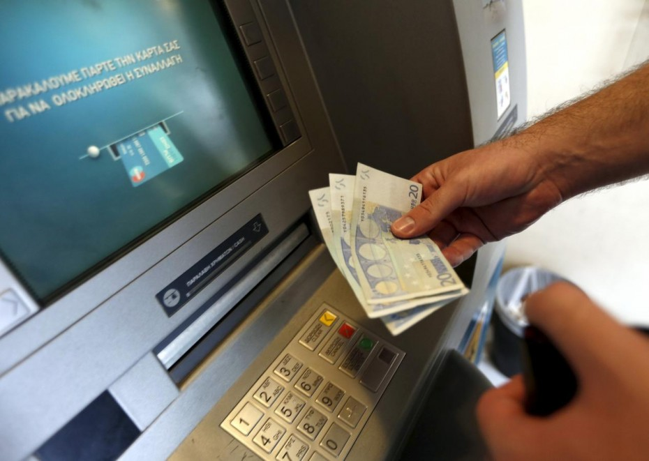 A man withdraws sixty Euros, the maximum amount allowed after the imposed capital controls in Greek banks,  at a National Bank of Greece ATM in Piraeus